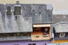 Cochem, Pfalz, Niemcy, Czerwiec 10, 2018: Odgórny widok mężczyzna obsiadanie na czytaniu i balkonie książka zdjęcia royalty free