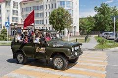 Coches adornados con las banderas que conducen alrededor de las calles de la ciudad en celebra Imagenes de archivo