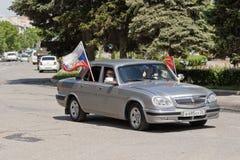 Coches adornados con las banderas que conducen alrededor de las calles de la ciudad en celebra Foto de archivo libre de regalías