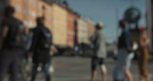 Coches borrosos y gente que caminan y que montan en bicicleta en una intersección en Estocolmo central almacen de metraje de vídeo