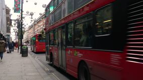 Coches, compradores, ciclista, taxis, autobuses rojos de Londres del autobús de dos pisos, calle de Oxford, Londres, Inglaterra almacen de video