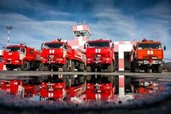 Coches de bomberos del campo de aviación con la reflexión en un charco imagen de archivo libre de regalías