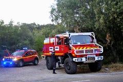 Coches de bomberos en la entrada de un camino forestal Imagen de archivo libre de regalías