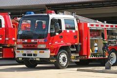 Coches de bomberos rojos y blancos en un alto día del peligro del fuego Foto de archivo