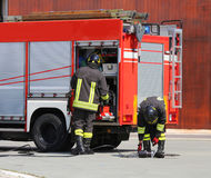 Coches de bomberos y bomberos con los uniformes Foto de archivo