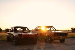 Coches de carreras en la puesta del sol Imagen de archivo libre de regalías
