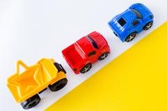 Coches de los juguetes de los niños en el fondo blanco y amarillo Visión superior Endecha plana Para el texto imagenes de archivo