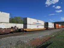 Coches del ferrocarril con los envases intermodales de caza de NFI RoadRail, de JB, de rápido y Schneider que pasa por Haverstraw Imágenes de archivo libres de regalías