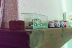 Coches del juguete en fila en una barra de madera sobre una chimenea foto de archivo