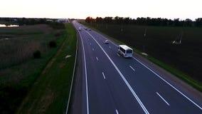 Coches del tráfico de la carretera en la carretera Campos de trigo verdes en la puesta del sol de una altura, camino pavimentado  metrajes