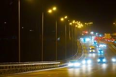 Coches del tráfico de la carretera en la noche blured Coches que mueven encendido el camino en bri Imagen de archivo libre de regalías