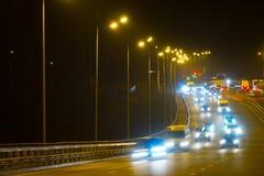 Coches del tráfico de la carretera en la noche blured Coches que mueven encendido el camino en bri Fotografía de archivo
