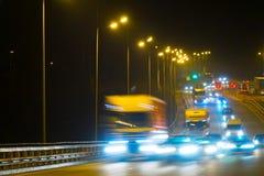 Coches del tráfico de la carretera en la noche blured Coches que mueven encendido el camino en bri Foto de archivo libre de regalías