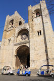 Coches del tuk de Tuk delante de la catedral de Lisboa, Portugal Fotografía de archivo