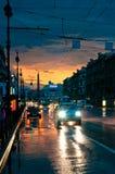 Coches en el camino mojado en la noche Foto de archivo libre de regalías