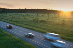 Coches en el movimiento en la carretera con puesta del sol Imagenes de archivo