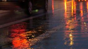 Coches en el tráfico, linternas en lluvia en el asfalto, visión abajo La lluvia golpea los charcos en la noche Reflexión de las l metrajes