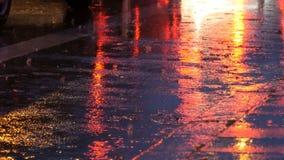 Coches en el tráfico, linternas en lluvia en el asfalto, visión abajo La lluvia golpea los charcos en la noche Reflexión de las l almacen de metraje de vídeo
