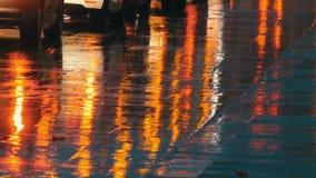 Coches en el tráfico, linternas en lluvia en el asfalto, visión abajo La lluvia golpea los charcos en la noche Reflexión de las l almacen de video