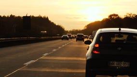 Coches en la carretera alemana del autobahn en la naranja de la puesta del sol almacen de video