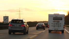 Coches en la carretera alemana del autobahn en la puesta del sol metrajes