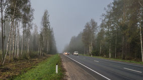 Coches en la carretera en niebla Imagenes de archivo
