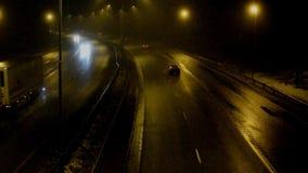 Coches en la carretera en la noche de niebla almacen de video
