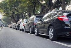 Coches en la línea, fila de coches parqueados en el borde de la carretera de la calle de la ciudad Imagen de archivo