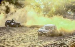 2 coches en la raza en el polvo fotografía de archivo libre de regalías