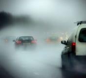 Coches en un camino en lluvia pesada y niebla Imagen de archivo libre de regalías