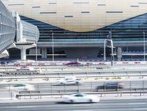 Coches en una carretera con la estación de metro futurista en Dubai Foto de archivo
