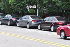 Coches estacionados al lado de la calle Fotos de archivo