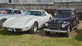 Coches Fiat 500 Topolino y Chevrolet Corvette C3 del vintage imagen de archivo
