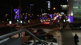 Coches móviles, gente que camina y edificios con la iluminación en la ciudad de la noche desenfocado metrajes