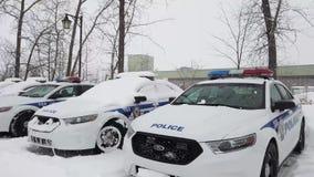 Coches policía hermosos parqueados en aparcamiento después de tormenta de la nieve almacen de metraje de vídeo
