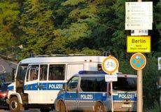 Coches policía al lado de la ciudad de Berlín de la señal de tráfico Foto de archivo libre de regalías