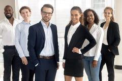 Coches profesionales sonrientes de los líderes que miran la cámara con los empresarios de los empleados imágenes de archivo libres de regalías