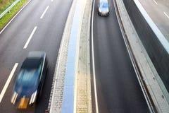 Coches que apresuran en carriles de la carretera foto de archivo libre de regalías