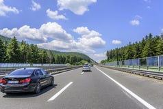 Coches que apresuran en el Autobahn entre paisaje de la montaña Imágenes de archivo libres de regalías