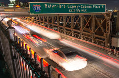 Coches que apresuran en el puente de Brooklyn - Nueva York por noche Foto de archivo libre de regalías