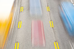 Coches que apresuran a lo largo de la carretera Foto de archivo libre de regalías