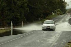 Coches que cruzan el camino inundado Foto de archivo libre de regalías