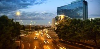 Coches que mueven encendido el camino en ciudad en la noche Imagen de archivo libre de regalías