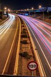 Coches que pasan en una carretera en Palma de Mallorca en la noche imagen de archivo libre de regalías