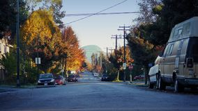 Coches que pasan a través de suburbios bonitos en la salida del sol metrajes
