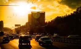 Coches que se mueven en ciudad en la puesta del sol contra el sol Fotos de archivo libres de regalías