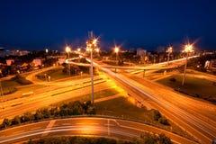 Coches que se mueven a través de la intersección de la carretera en la oscuridad Fotos de archivo