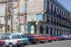 Coches retros del color y edificio quebrado en el centro de la ciudad de La Habana Imagenes de archivo