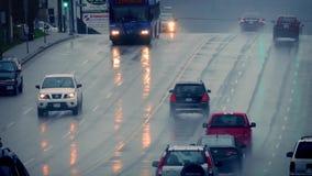 Coches y autobús en el camino mojado en ciudad