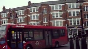 Coches y autobuses de dos plantas rojos que circulan en el cruce giratorio en la colina Broadway, Londres, Inglaterra de Muswell almacen de metraje de vídeo